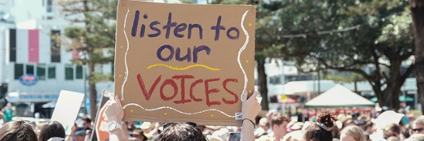 Person at a rally holding sign saying 'Listen to our voices'