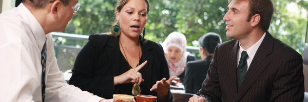 Woman speaking to two men