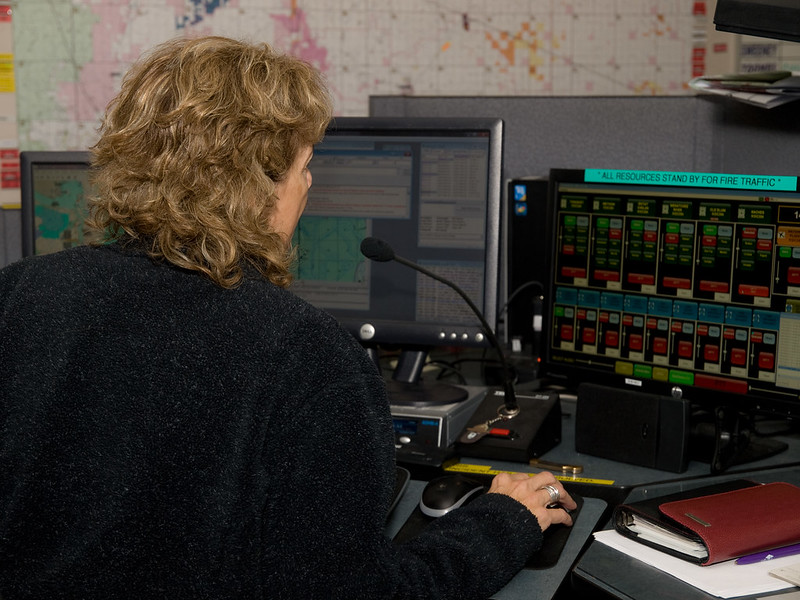 Woman sitting at a desk in front of computer screens and a radio with a microphone.