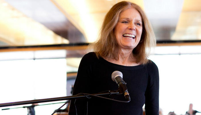 Gloria Steinem is at a podium in front of a microphone and is laughing.  She is wearing a black, full sleeve top.