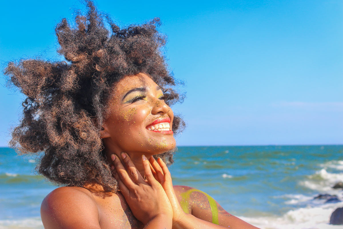 Image of a black woman on a beach, smiling joyfully into the sun. She has sand on her face and shoulders, and her hair is flowing in the breeze. In the background, waves crash against rocks on the shore.