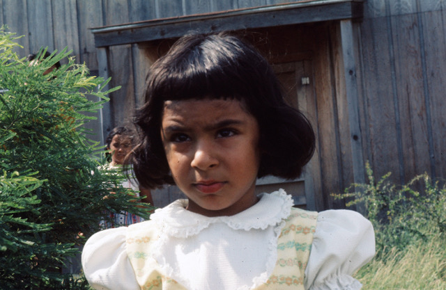 young indian girl scowling, wearing frilly white and yellow dress.  standing outside in front of wooden structure.