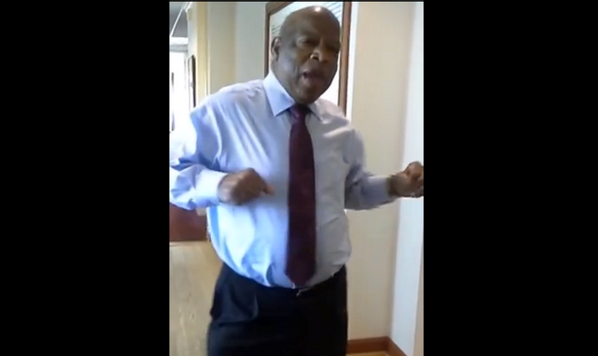 Screen shot of Congressman John Lewis dancing in an office hallway.  He is wearing business attire.