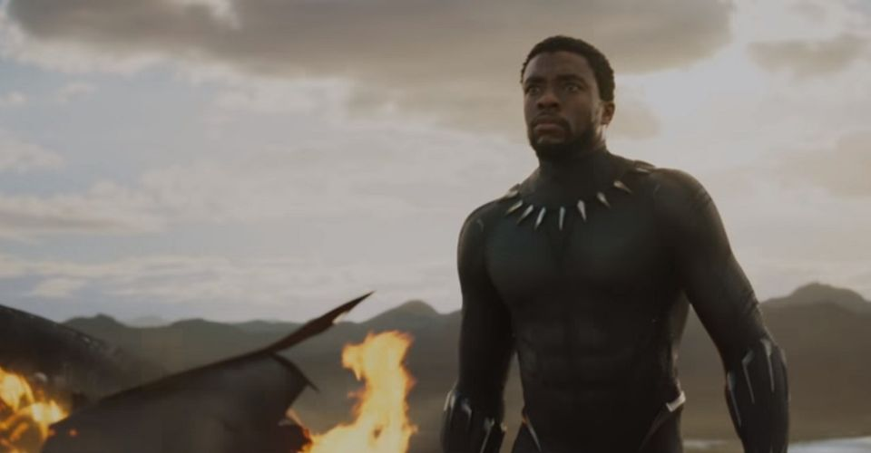 image of actor Chadwick Boseman as King T'challa in Black Panther; a black man in a black bodysuit adorned with metal teeth stands with open arms in front of a cloudy sky.