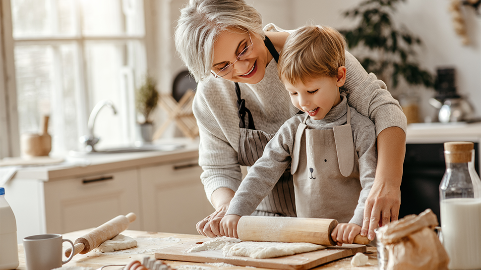 Photo of a grandmother and grandchild rolling out dough in a kitchen.