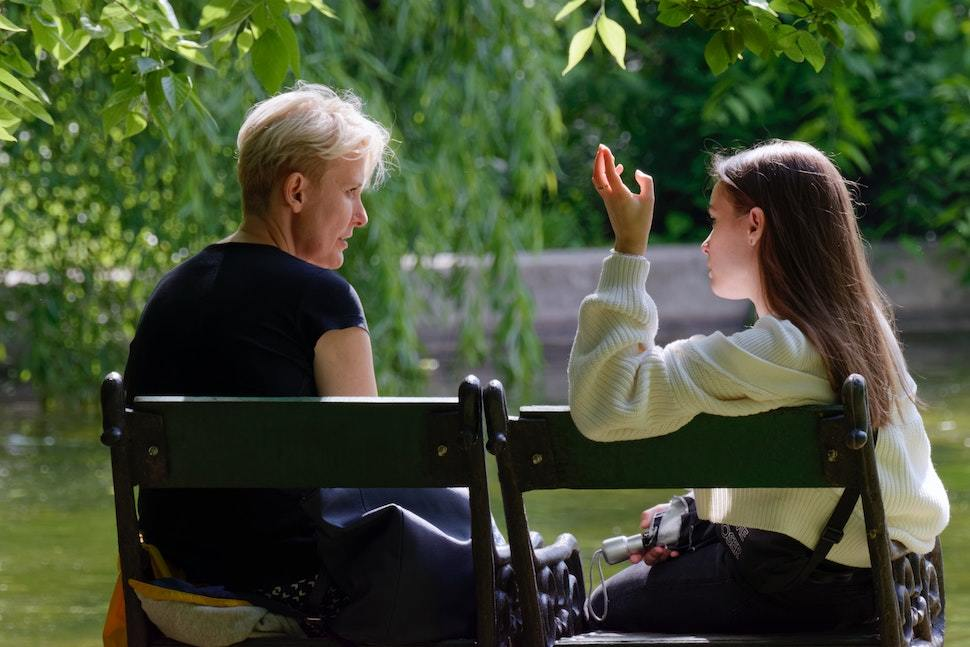 Mother and daughter talking outdoors