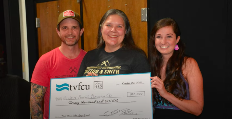 Representatives of Hutton and Smith Brewing Company receiving a check from TVFCU