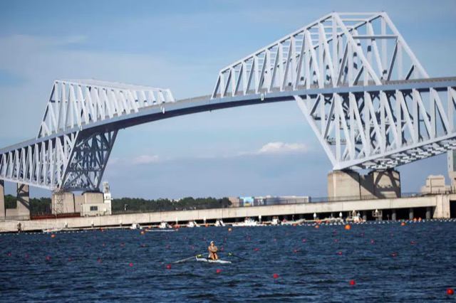 truss bridge spanning Toyko Bay with kayaker and red buoys