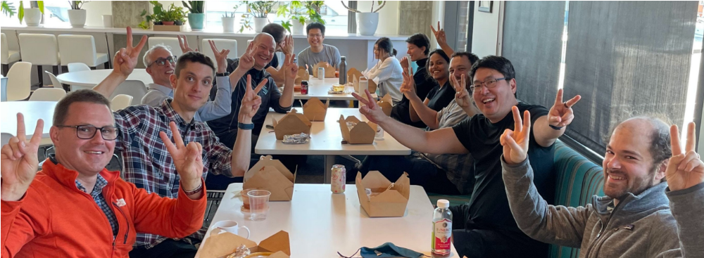 A group photo of new AI2 team members eating lunch together at AI2 headquarters.