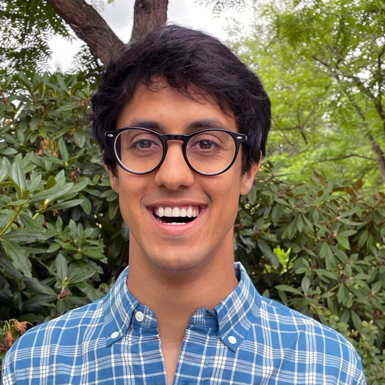 Smiling person in a plaid shirt with glasses
