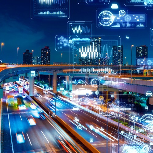 A photo collage of cars on a highway at night with city buildings in the background and various glowing graphs, charts, and symbols int he air and sky around the scene.