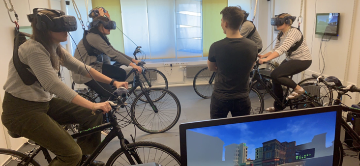 Research participants pedaling on bikes while wearing VR-glasses.