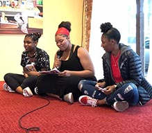 three Black girls sitting on the floor while one speaks into a microphone