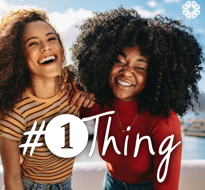 two Black women laughing together with #1Thing logo