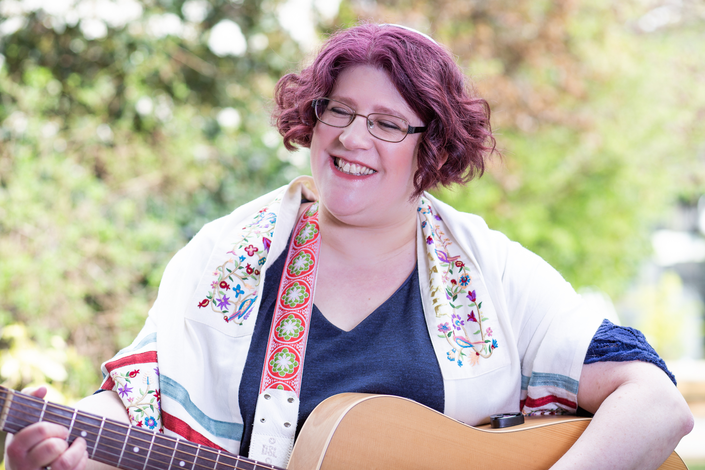Mich Sampson - picture shows smiling woman wearing a tallit (prayer shawl) and playing the guitar. There is a leafy, sunny background.