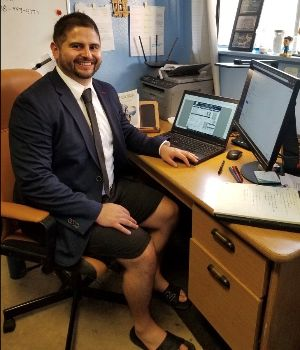 Victor Zendejas poses at his desk in suitcoat and tie over shorts.