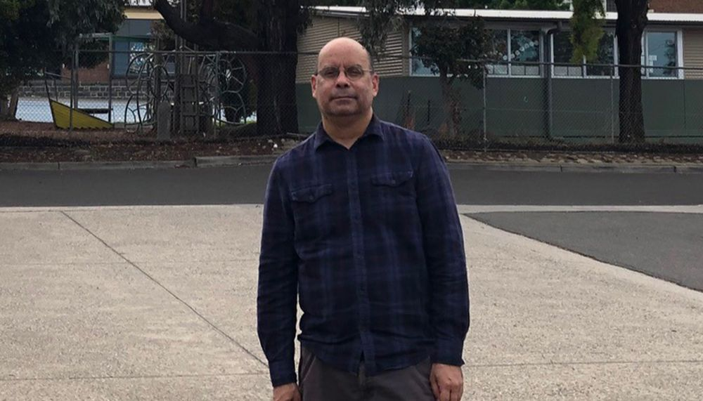 Photo of Ron Davis in a dark blue check shirt, standing outside.