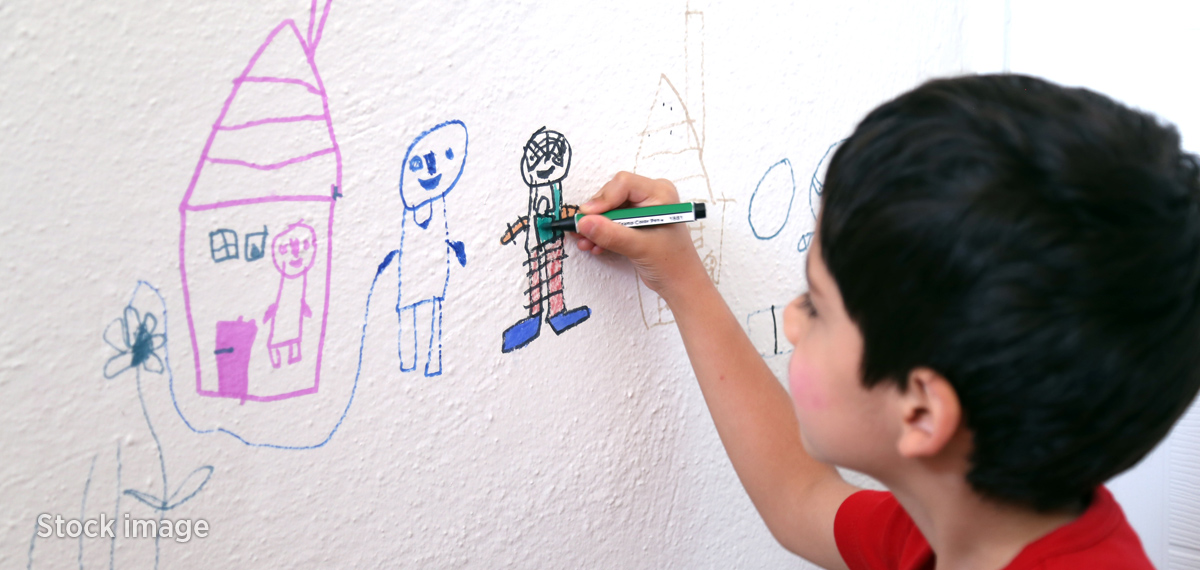 Picture of a young boy drawing a picture of people and houses.