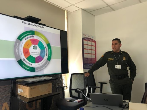 In the picture to the left, Captain Escalante is presenting on the Peacebuilding Model used by the National Police of Colombia. In the picture to the right, Kroc School students are walking on the floor made from the firearms handed over by the FARC as part of the peace process.