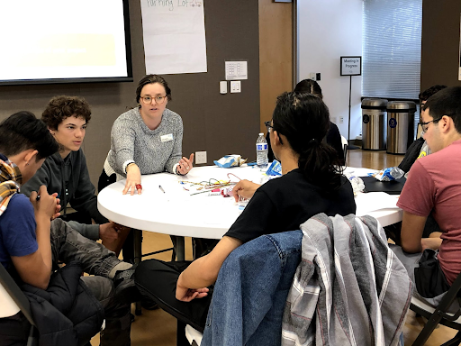 Daria helps a group of students brainstorm project ideas related to food insecurity.
