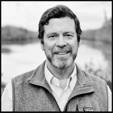 black and white image of Executive director David Farren He has short dark hair, dark and grey moustache and beard facial hair and is smiling