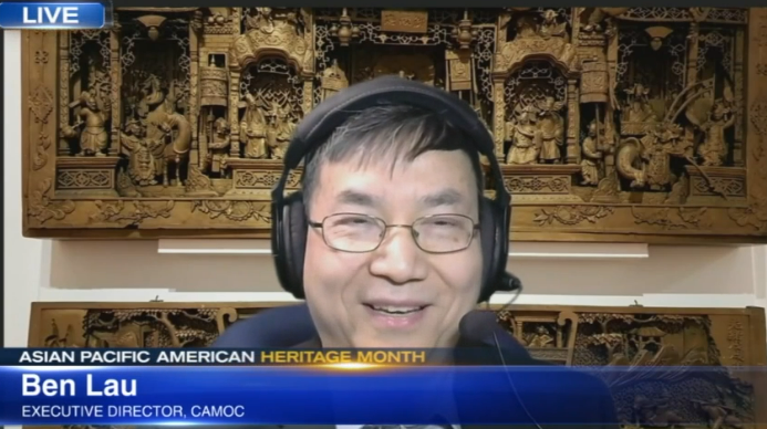 Ben Lau is a man wearing glasses and a headset; behind him is an intricate wooden carving
