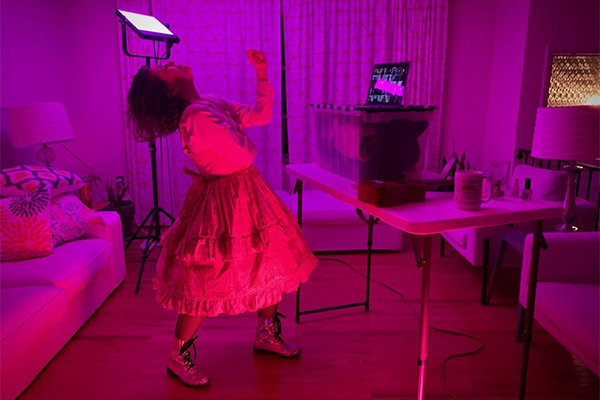 Photo of Siobhan O'Loughlin dancing in front of a computer in a room with pink lighting.