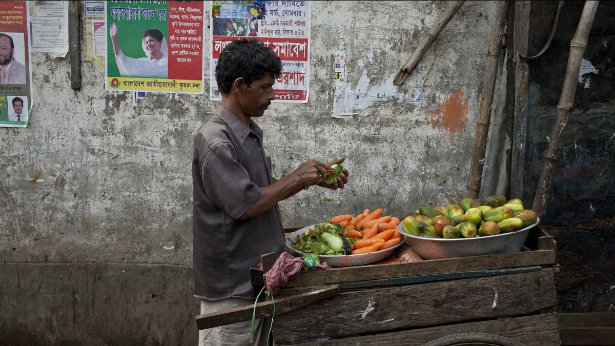 A vegetable seller peels a cucumber in Koral slum, Dhaka. Getting nutritious food every day is a challenge in large cities due to the high cost of living (Photo: Conor Ashleigh, AusAID, via Flickr, CC BY 2.0)