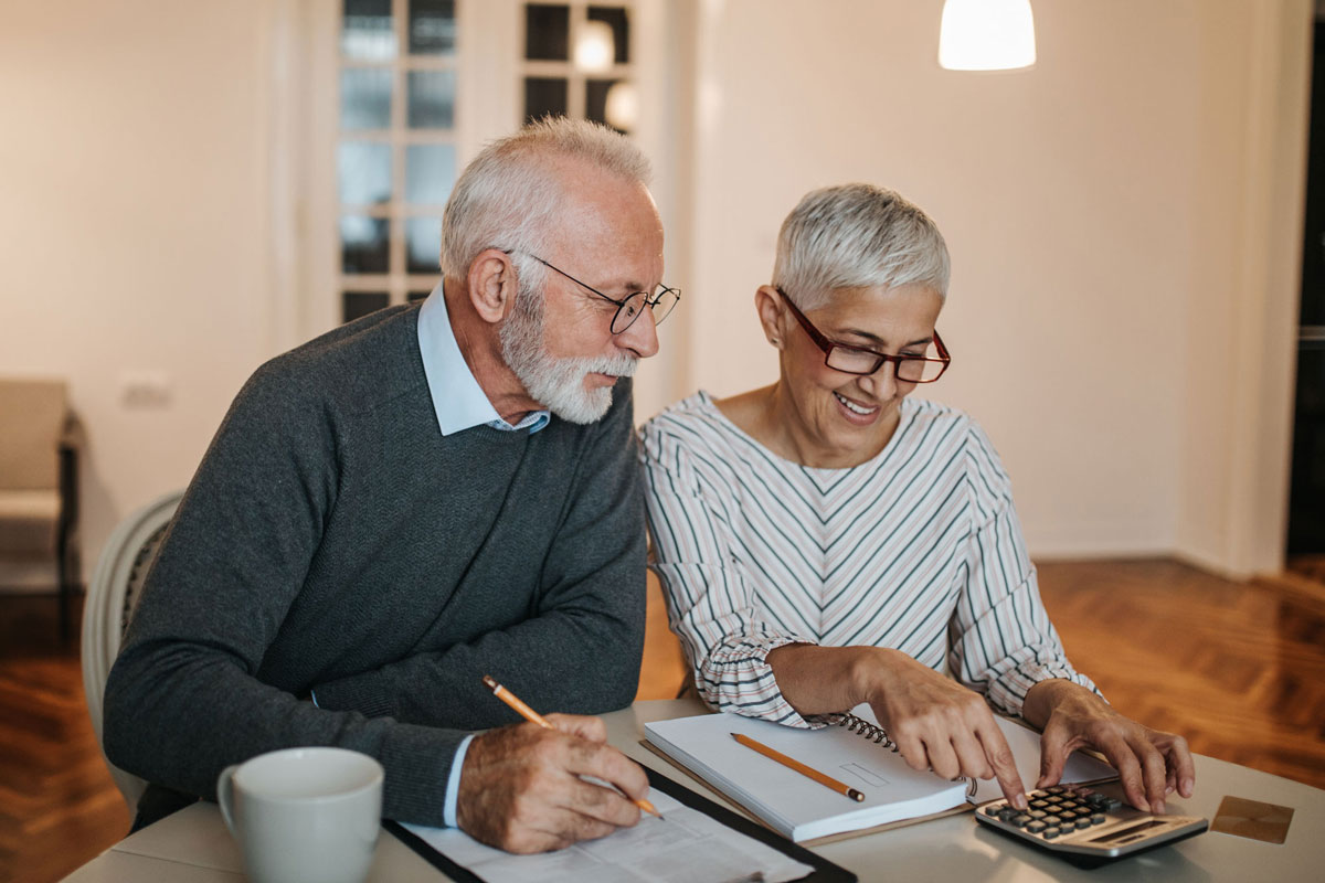 An older man and woman look over financial statements as they make plans for charitable giving