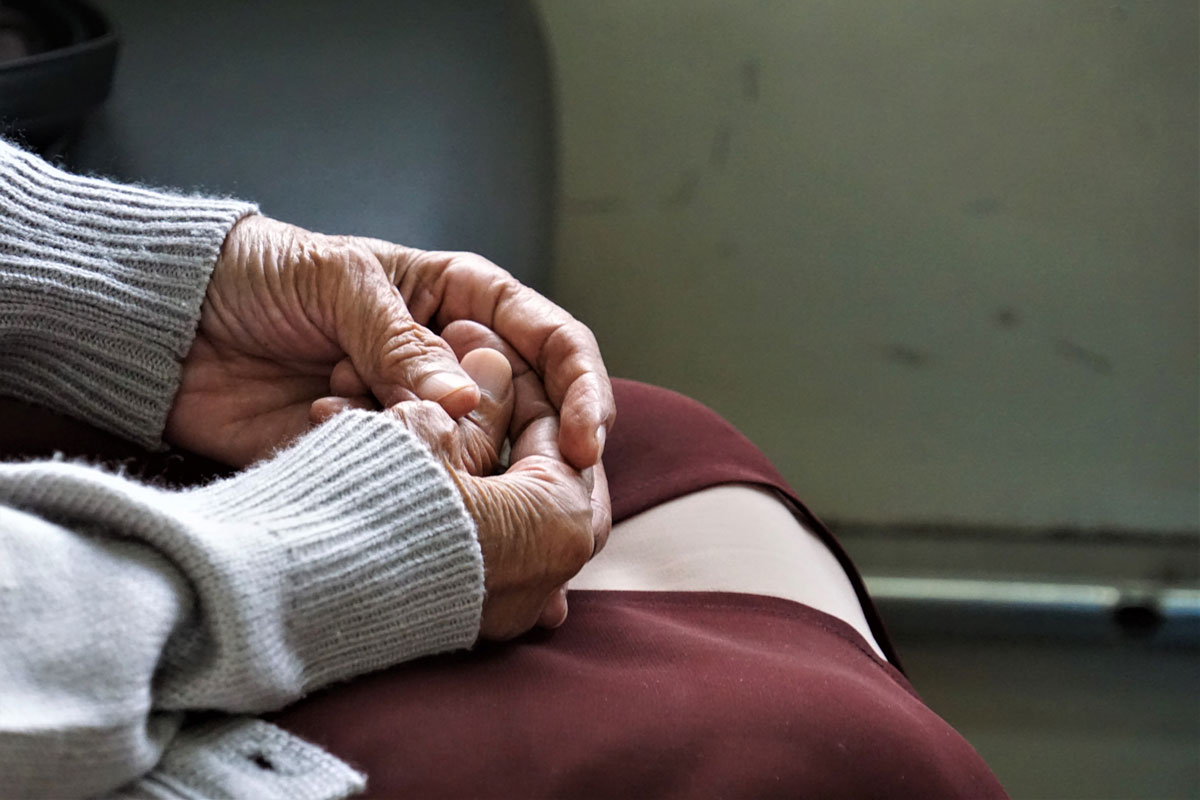 close up on an isolated senior with hands in lap