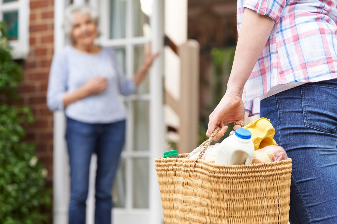 a volunteer delivers groceries to an older woman at home