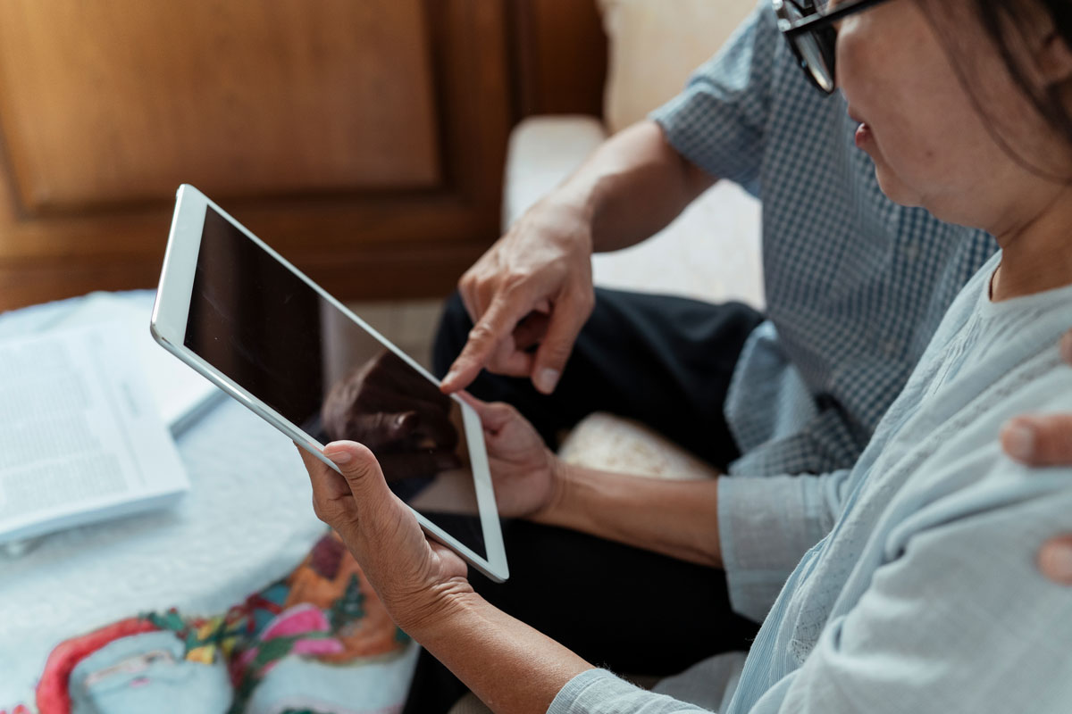 An older woman learns to use a tablet