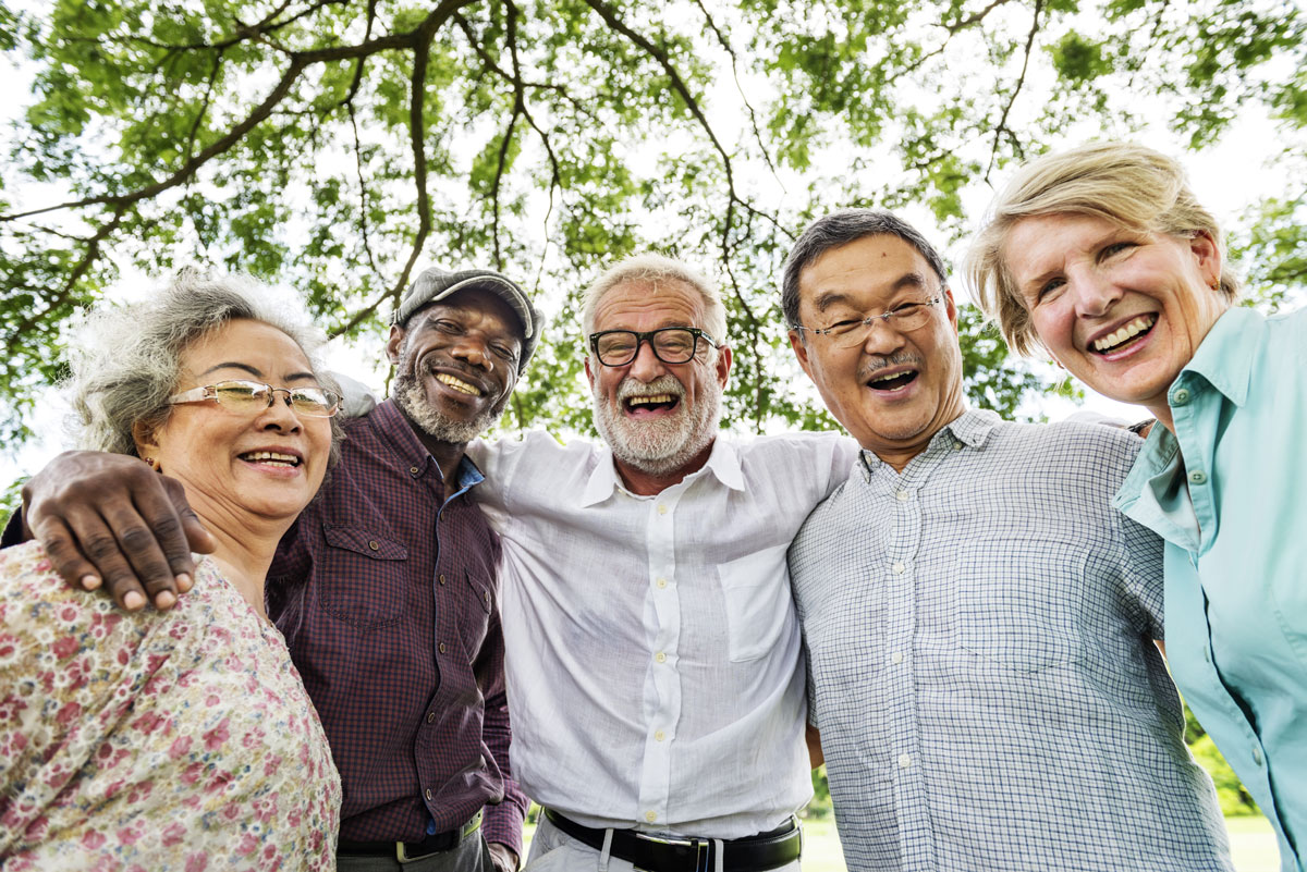 A group of older people huddled together and smiling