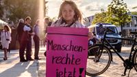 Eine kleinwüchsige Frau steht auf dem Bürgersteig und hält ein pinkes Schild hoch. Darauf steht: Menschenrechte jetzt!