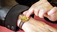 Eine Armbanduhr auf einem handgelenk, mit der anderen hand fühlt die person die uhrzeit auf dem geöffneten gehäuse