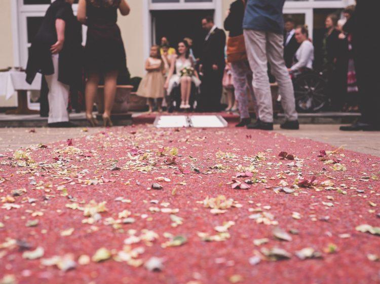 Auf einem roten Teppich liegen Rosenblätter. In der Entfernung ist ein BRautpaar, Gäste und eine Rollstuhlrampe zu sehen. Die Braut trägt ein weißes Kleid und sitzt im Rollstuhl.
