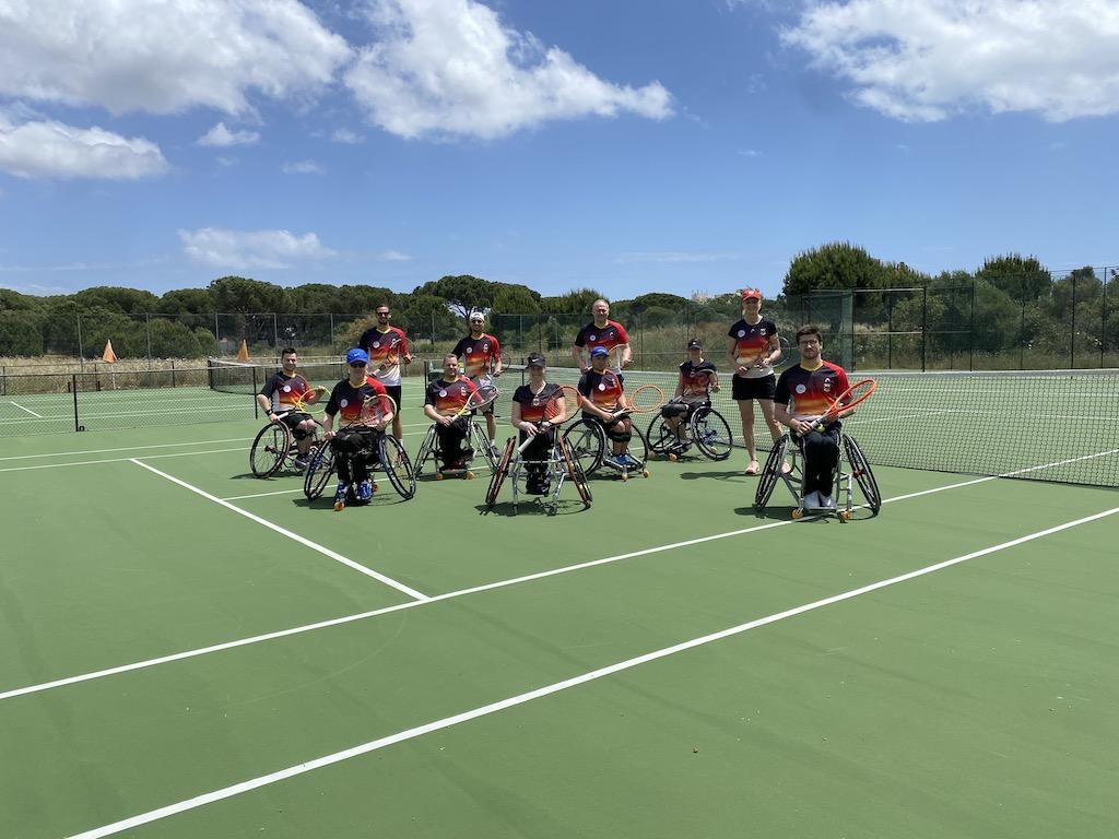 Foto der Deutschen Rollstuhltennis Nationalmannschaft. Mehrere Personen sitzen in Rollstühlen nebeneinander und halten Tennisschläger in der Hand. Das Foto wurde auf einem Tennisplatz draußen aufgenommen, die Sonne scheint und der Himmel ist blau.
