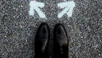 zwei schwarze schuhe auf dem asphalt, davor zwei pfeile in verschiedene richtungen