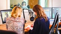 Zwei Frauen sitzen an einem Tisch vor Computerbildschirmen und Mikrofonen. Sie sind von hinten zu sehen.