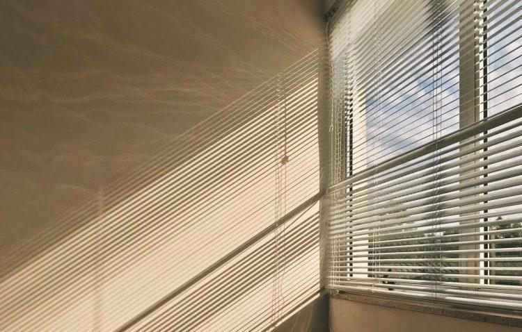 Durch die Lamellen einer Gardine scheint Sonnenlicht in ein leeres Zimmer.