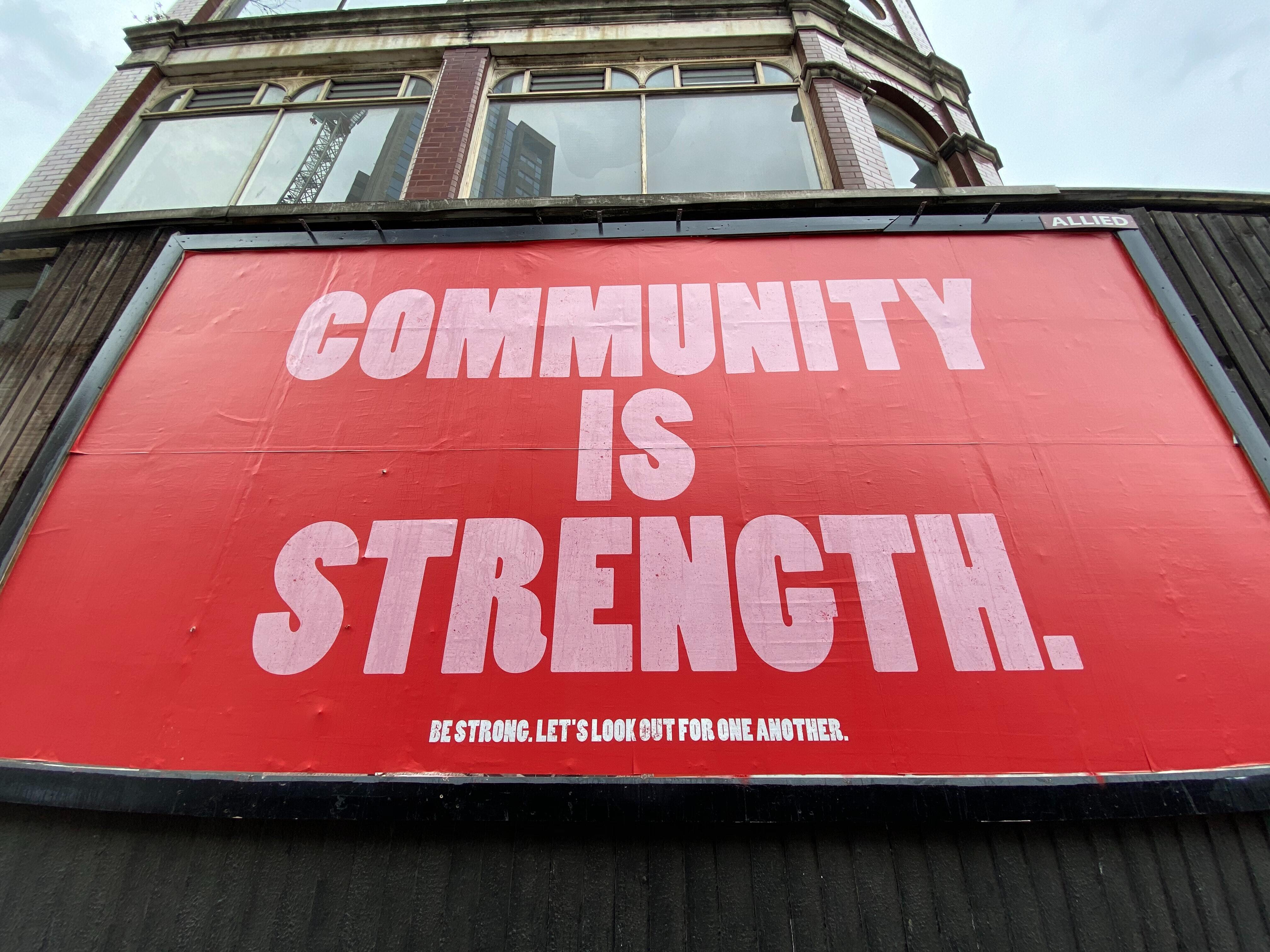 """Red billboard with the words """"community is strength"""" written on it."""