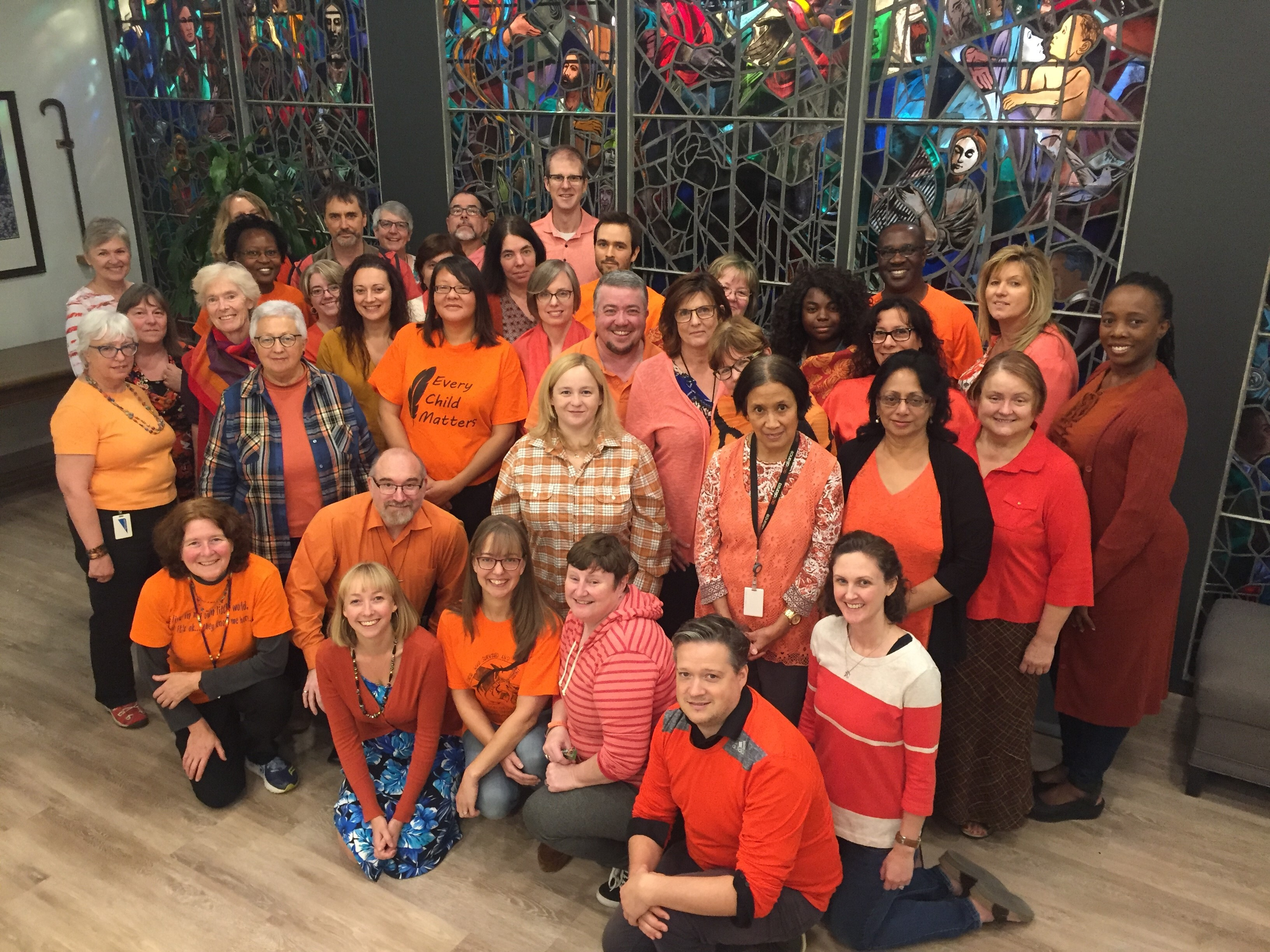 A photo from several years ago of General Council Office staff wearing orange shirts.