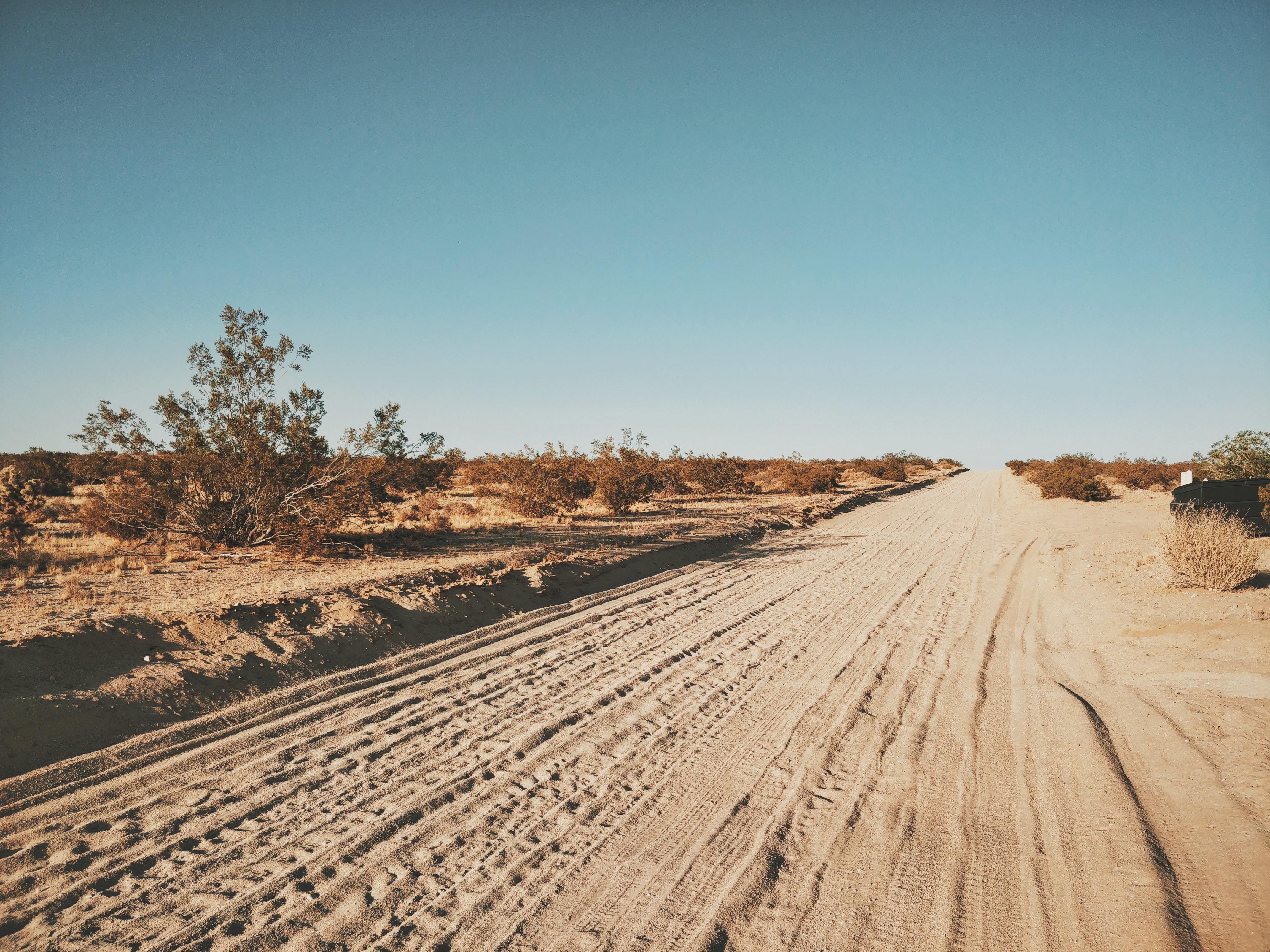 A dusty sand road and blue sky.
