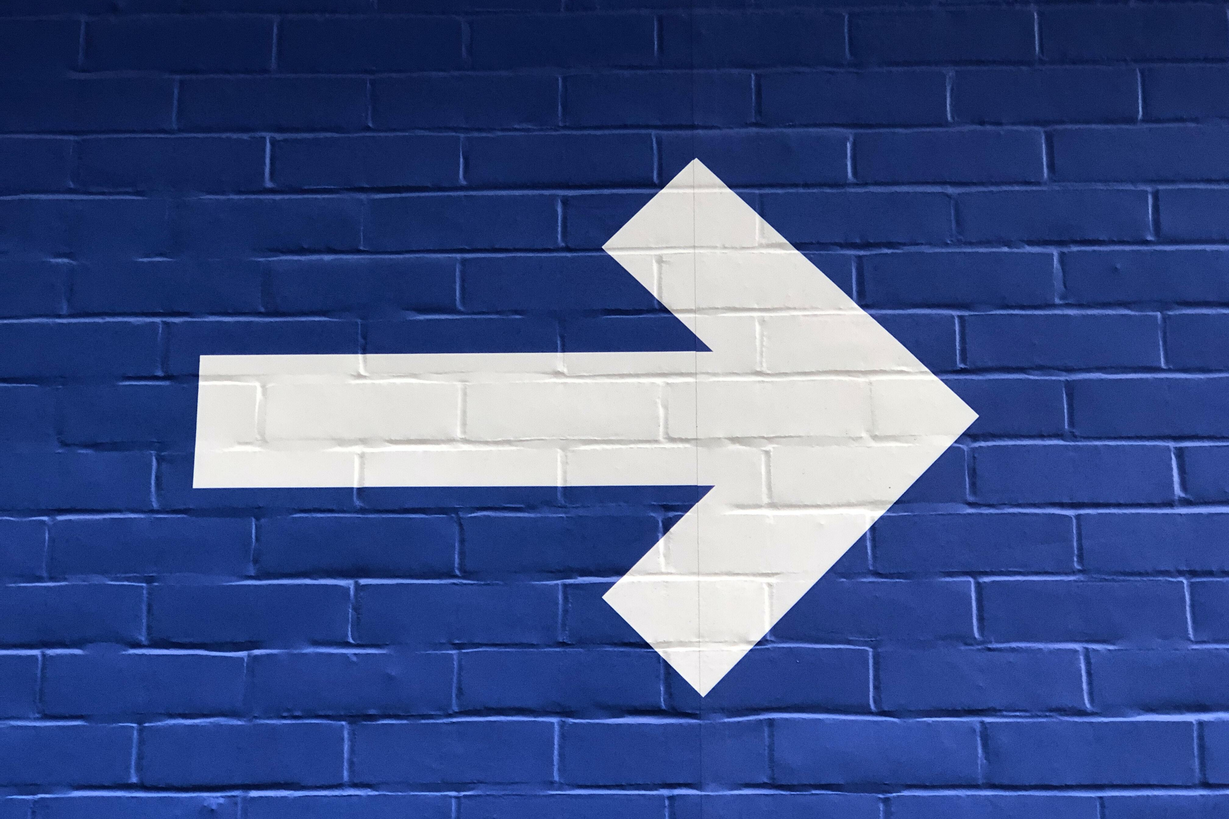 Image of a white arrow on a blue brick background.