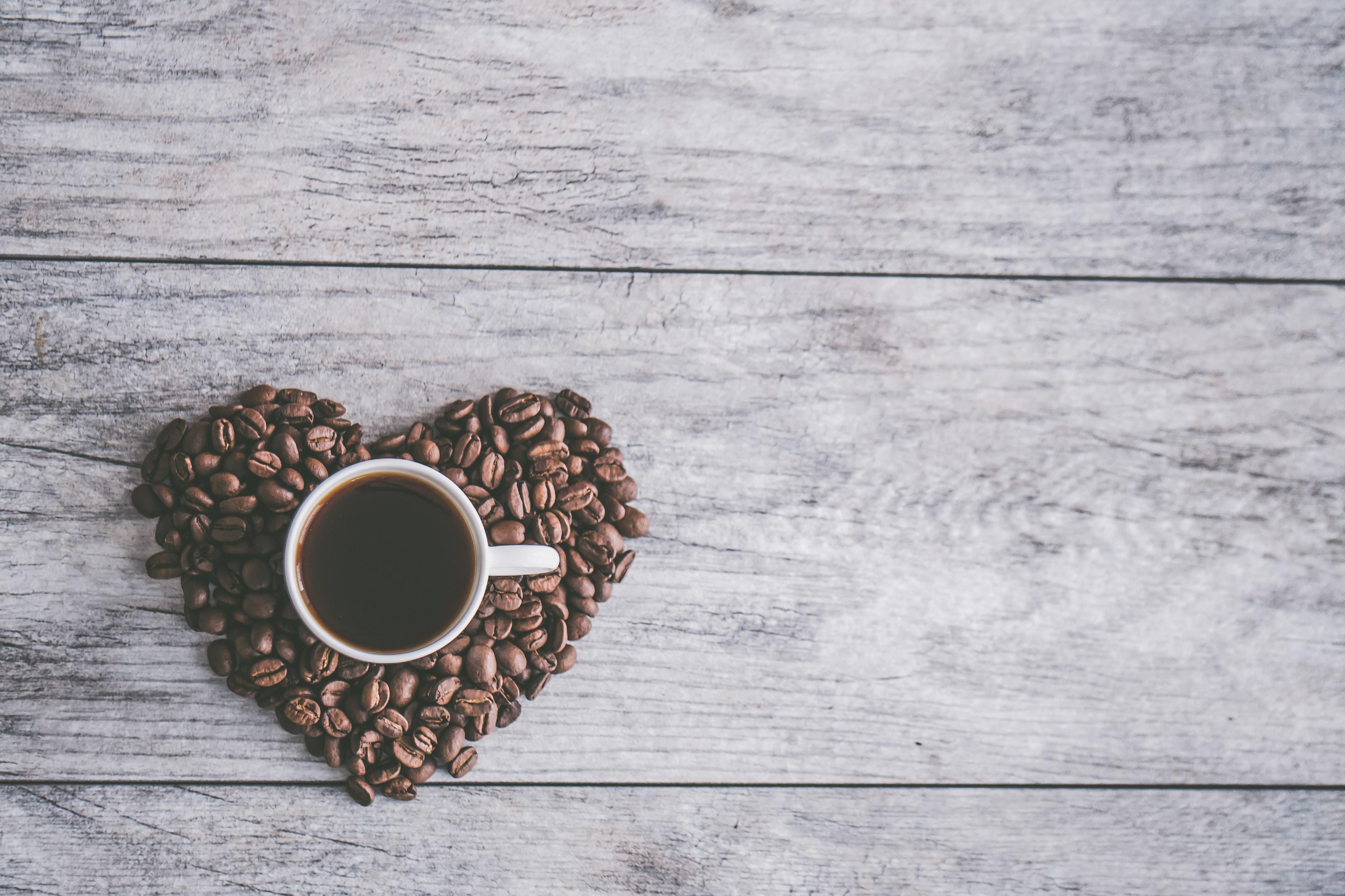 Birds eye photo of a cup of coffee on top of a heart made of coffee beans, on a wooden table.