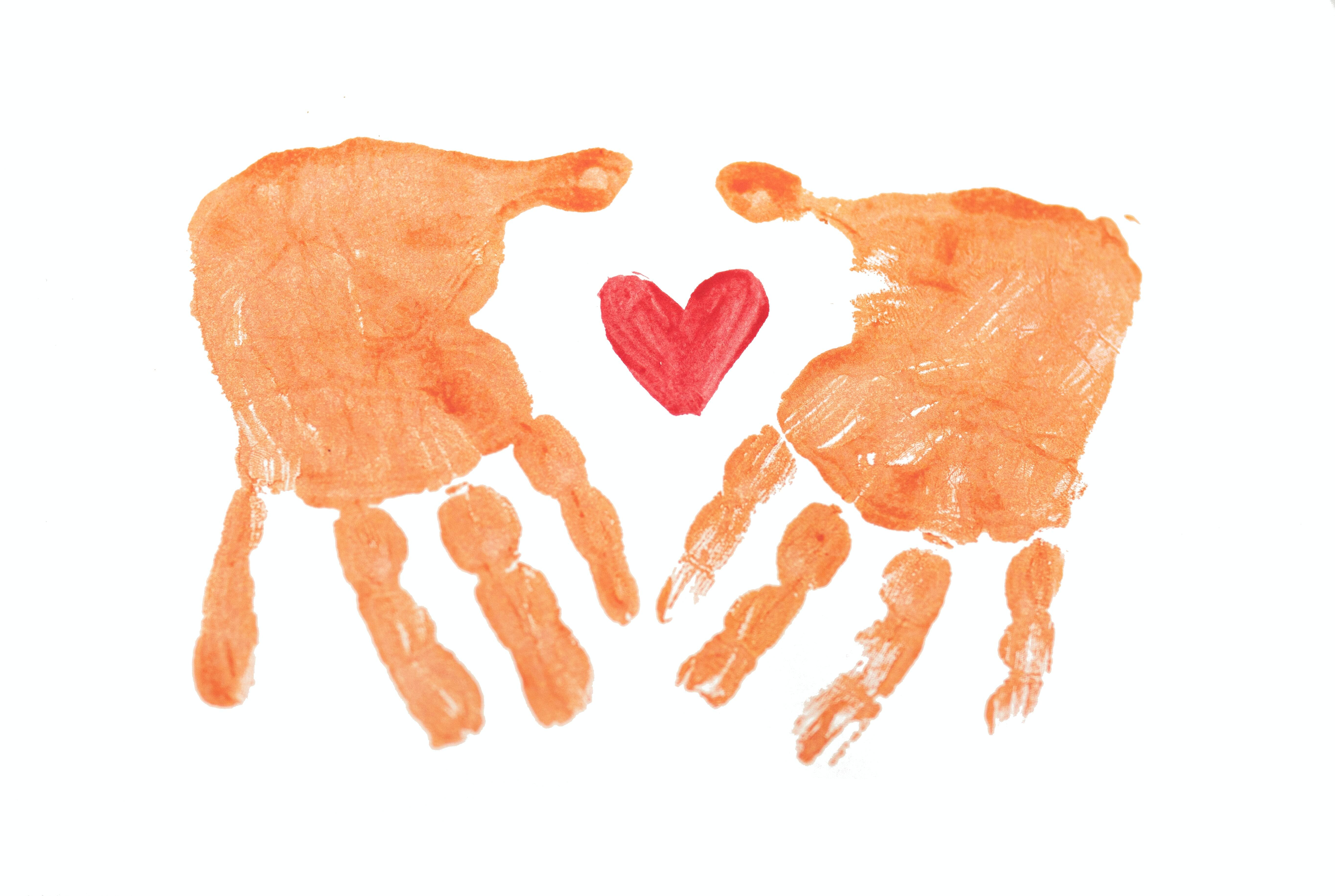 Two orange handprints around a painted red heart.