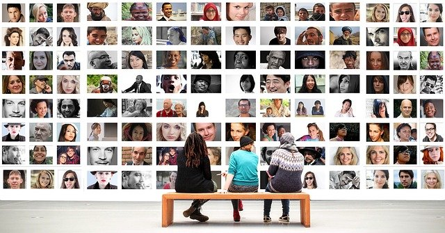 Photo of three people on a bench in a gallery, looking at a wall of photos of diverse people.