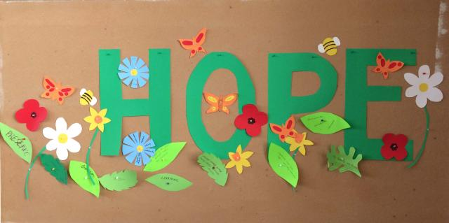 """The word """"hope"""" spelled out in green paper letters, surrounded by colourful paper flowers and leaves."""