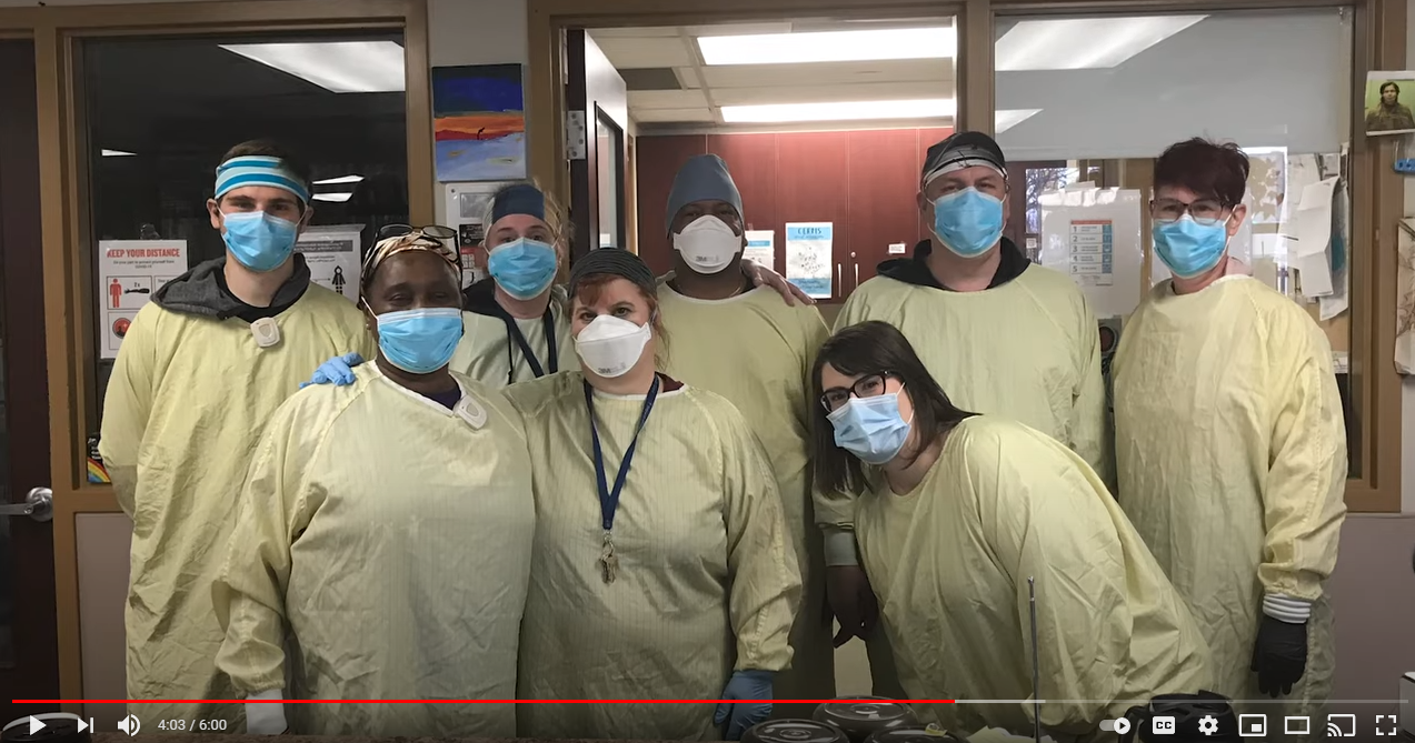 A screenshot from the music video, showing a group of masked but smiling healthcare workers.