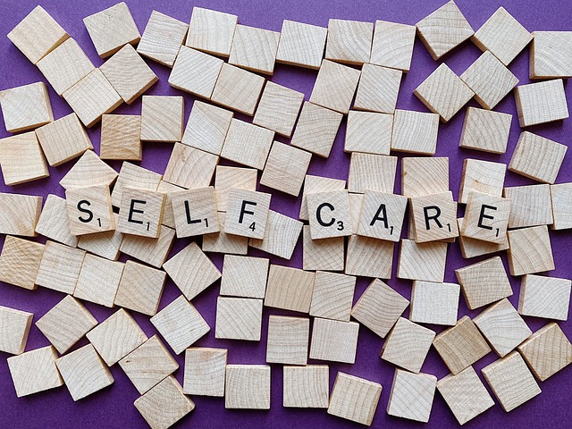 """Scrabble tiles spelling out the words """"self care""""."""